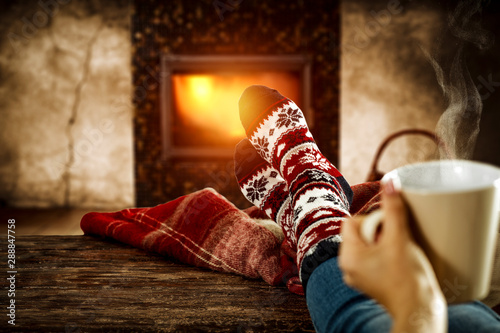 Fotografie, Tablou  Woman legs with christmas socks and home interior with fireplace
