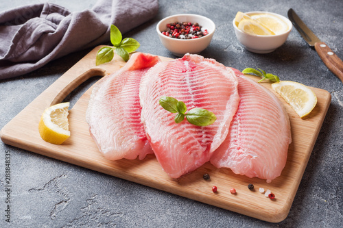 Raw fish fillet of tilapia on a cutting Board with lemon and spices. Dark table with copy space. - 288848335