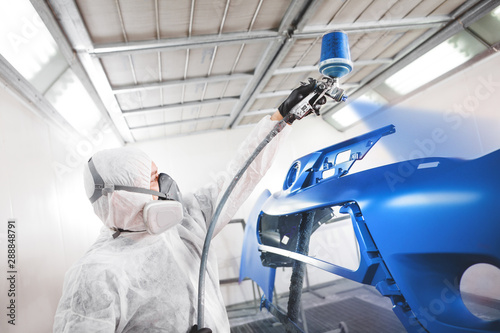 Photo Male worker in protective clothes and mask painting car bumper using spray paint