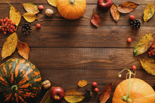 Autumn Frame Made Of Pumpkins, Dried Fall Leaves, Apples, Red Berries, Walnuts, Pine Cones On Wooden Table. Thanksgiving, Halloween, Autumn Harvest Concept. Flat Lay Composition, Top View, Copy Space