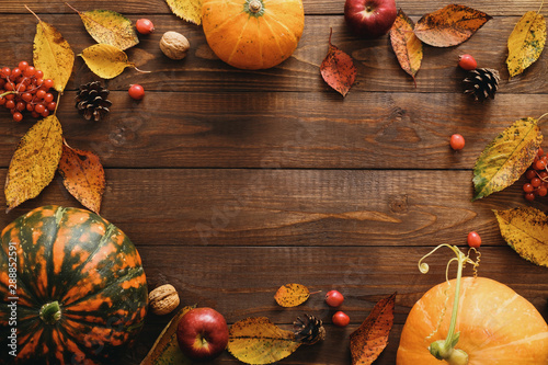 Foto Autumn frame made of pumpkins, dried fall leaves, apples, red berries, walnuts, pine cones on wooden table