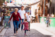 canvas print picture Young family with two small children walking outdoors in town on holiday.
