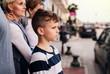 canvas print picture Side view of small boy with family standing outdoors in town.