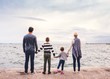 canvas print picture Rear view of young family with two small children standing outdoors on beach.