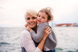 canvas print picture Young mother with small daughter standing outdoors on beach.