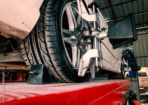 Tire clamped with lazer aligner undergoing auto wheel alignment in modern garage Wallpaper Mural