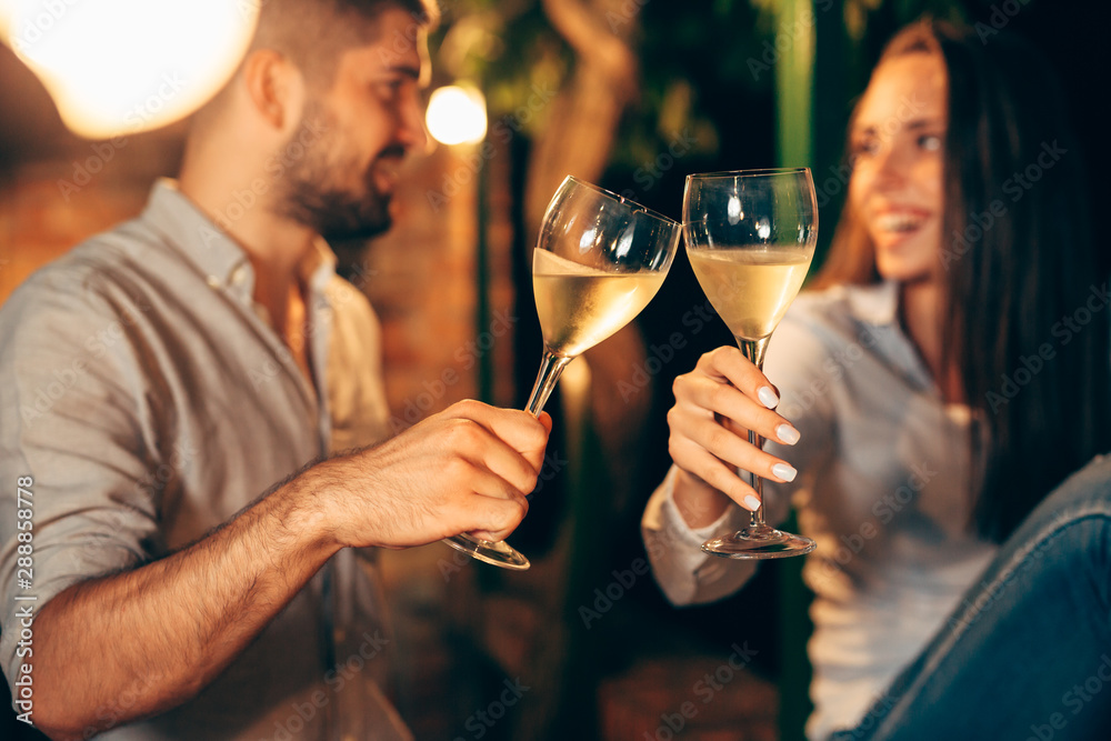 Fototapeta romantic couple drinking wine on backyard decking . evening scene