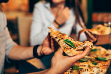Close Up Of People Eating Pizza.