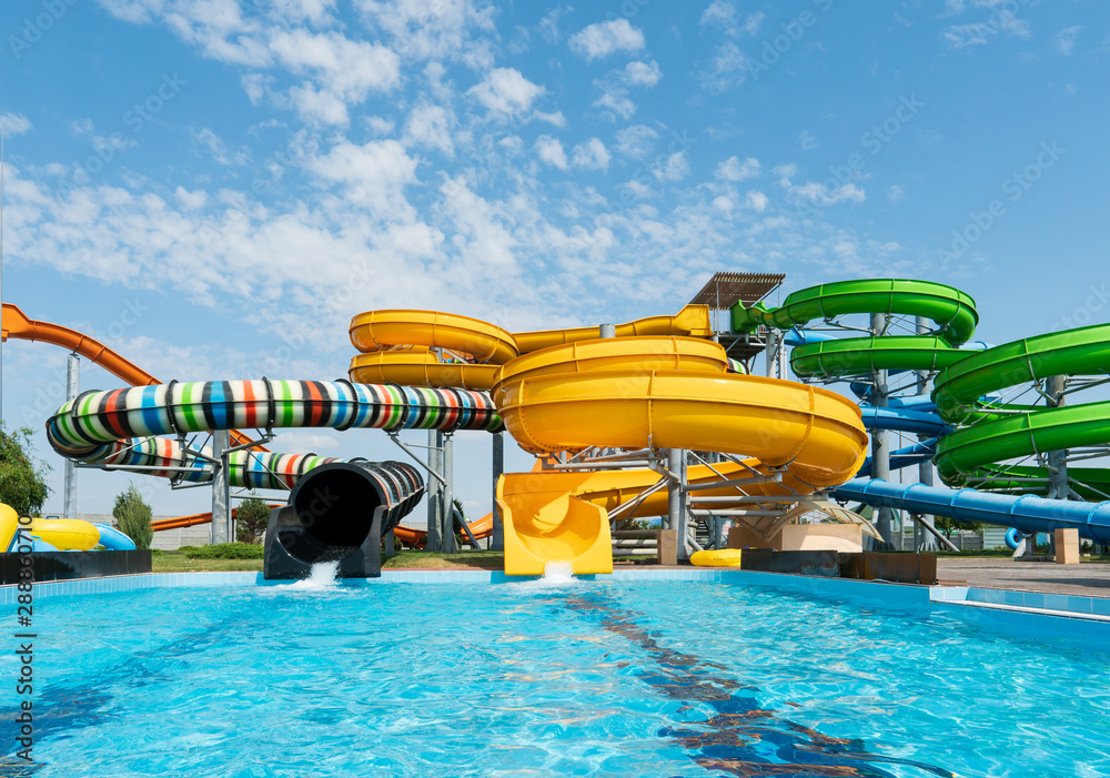 Fototapeta Water park, bright multi-colored slides with a pool. A water park without people on a summer day with a beautiful, cloudy blue sky