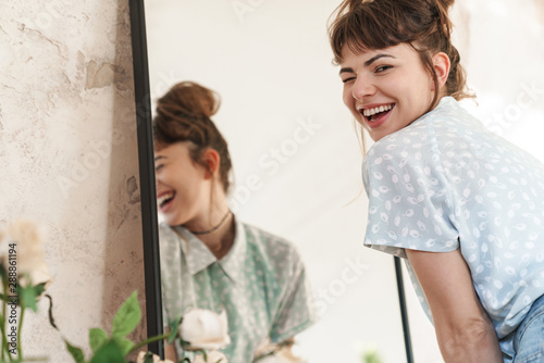 Emotional happy beautiful woman indoors at home posing near mirror looking camera.