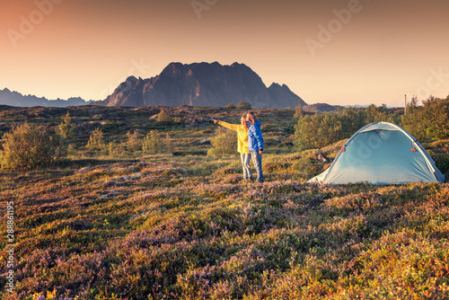 Spoed Fotobehang Kamperen A pair of female travelers stand next to a tent on the Lofoten Islands in Norway at sunset, trekking and wild camping lifestyle