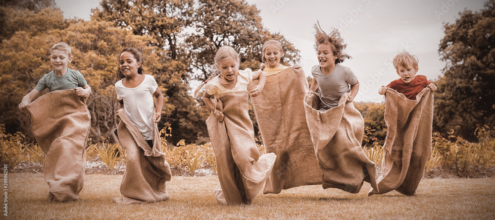 Fototapety, obrazy: Children having a sack race in park