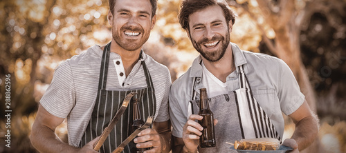 Obraz na płótnie Portrait of two happy men holding barbecue meal and beer bottle