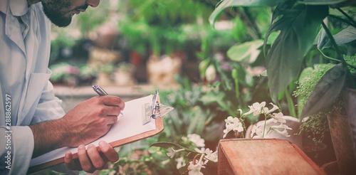 Male scientist writing in clipboard while examining plants Canvas Print