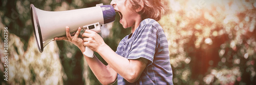 Photo A little boy is screaming with a megaphone