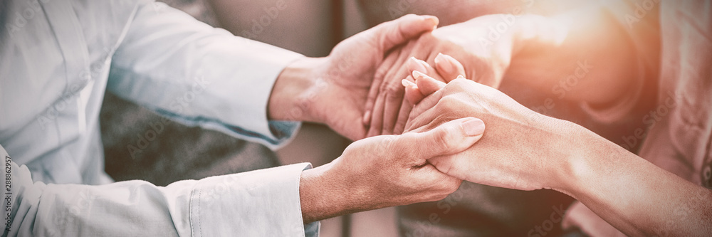 Fototapeta Midsection of therapist holding patient hands