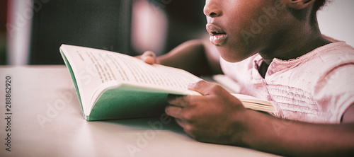 Girl reading a book in the classroom
