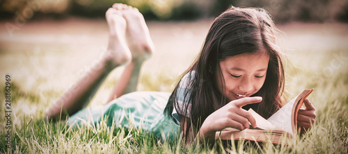 Smiling girl lying on grass and reading book in park