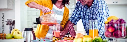 Photo Happy couple preparing smoothie in kitchen