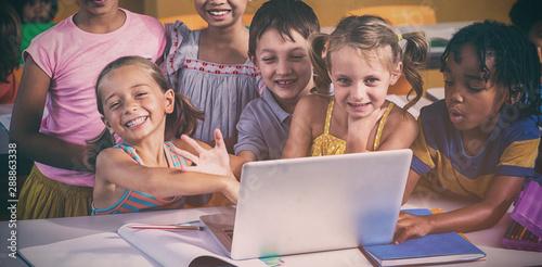 Smiling multi ethnic children using laptop