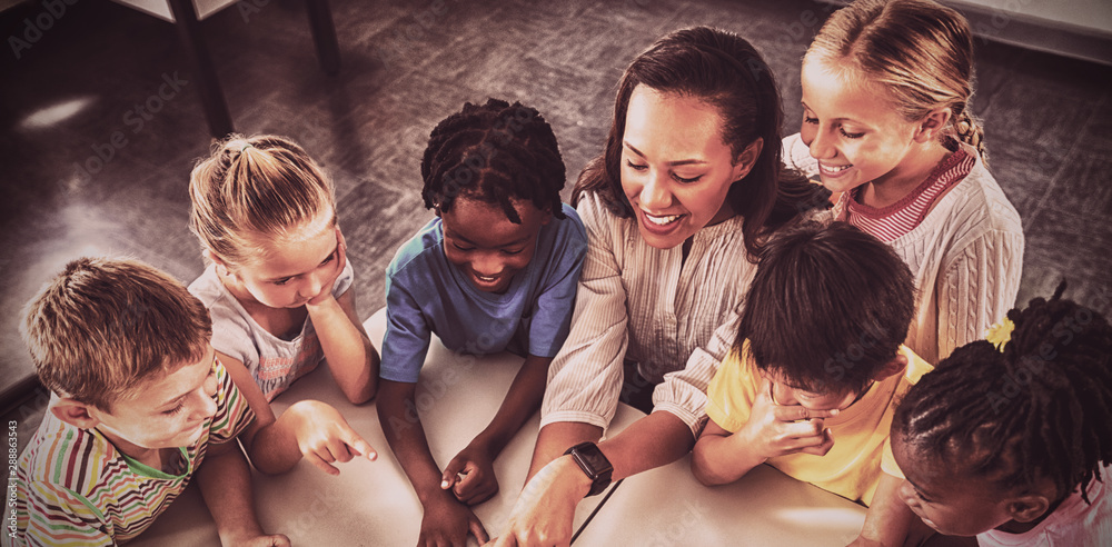 Fototapety, obrazy: High angle view of happy teacher and pupils using tablet pc