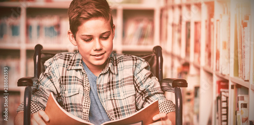 Disabled schoolboy reading book in library