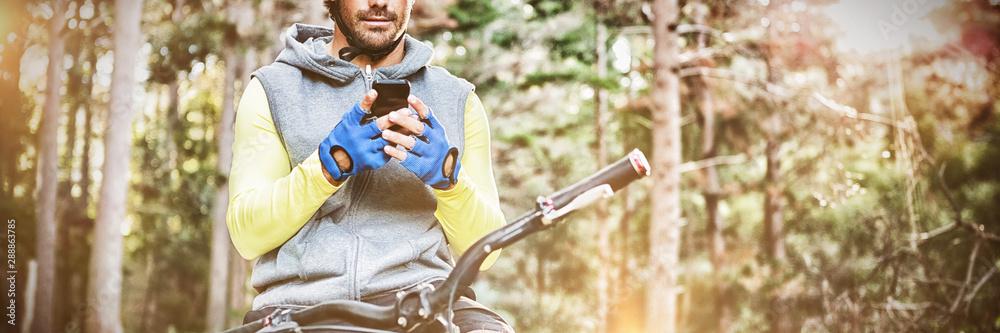 Fototapety, obrazy: Mountain biker using mobile phone