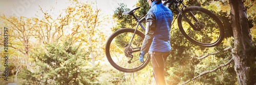 Mountain biker carrying bicycle looking at nature