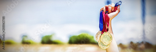 Photo Hand of female athlete holding gold medals