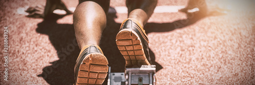 Feet of an athlete on a starting block about to run Canvas Print