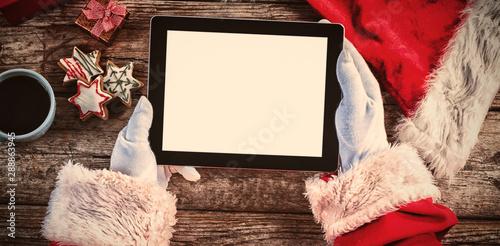 Santa claus holding digital tablet on wooden plank