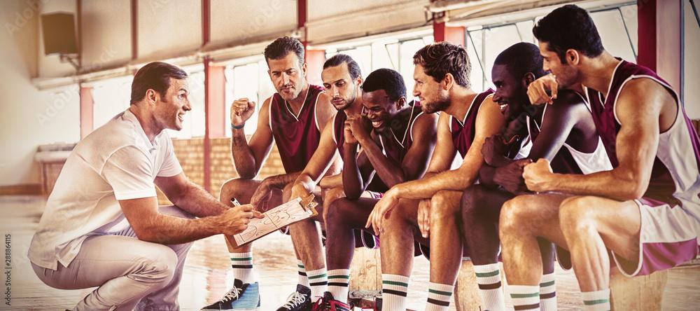Fototapeta Coach explaining game plan to basketball players