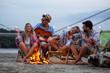 canvas print picture - Group of friends sitting around camp fire at the beach at the evening.They play guitar and singing.
