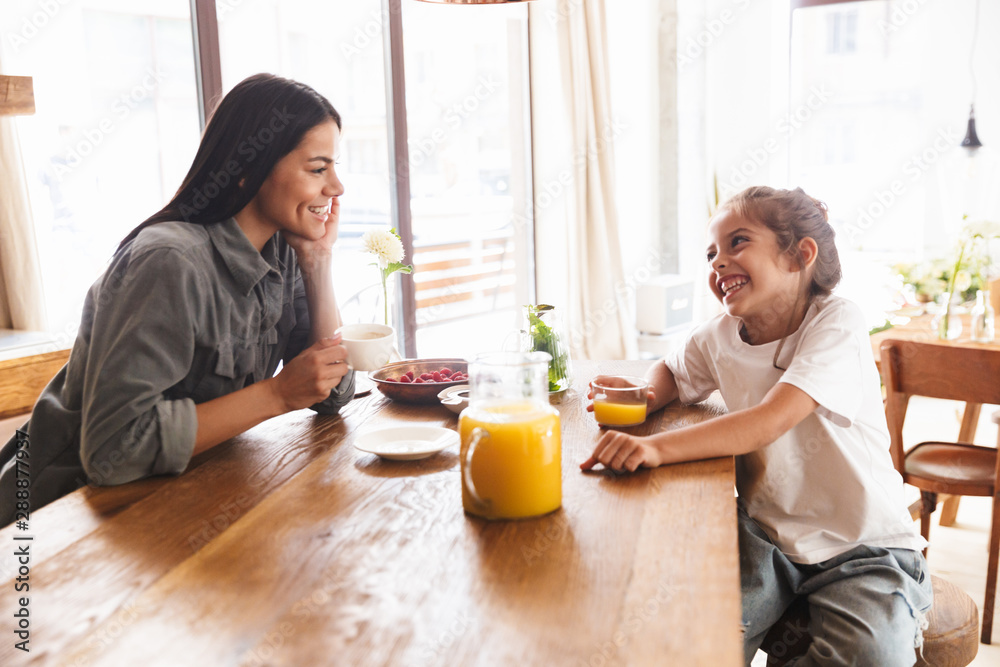Fototapeta Image of happy family mother and little daughter smiling and having breakfast at home in morning