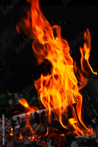 Burning wood logs, cooking on fire, warm evening, sparkles in the air, warm air from the fire