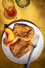 French Toast With Streusel And Peaches On Mustard Colored Background