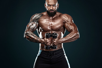 Fototapeta Sport Strong and fit man bodybuilder. Sporty muscular guy with dumbbells. Spot and fitness motivation.