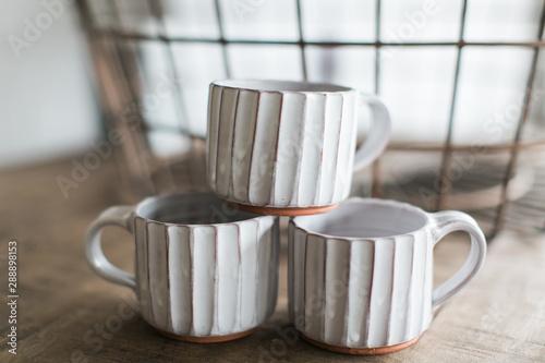 Three stacked handmade mugs with white glaze, custom pottery cups Fototapeta