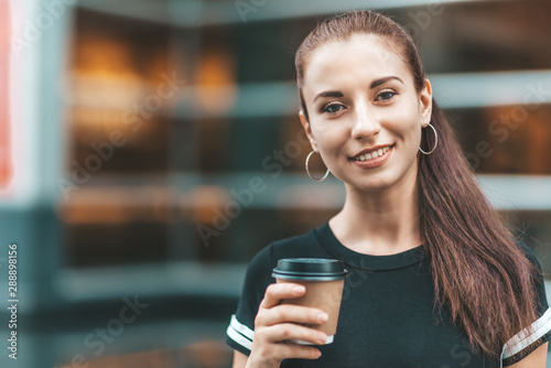 fototapeta na szkło Portrait of young cheerful woman looking at camera with a smile while walking outdoors and holding disposable paper cup with coffee in it. Horizontal shot. Selective focus. Front view
