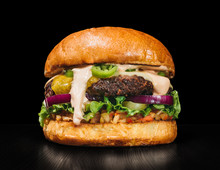 Craft Burger Is Cooking On Black Background. Consist: Sauce Salsa, Lettuce, Red Onion, Pickle, Cheese, Chilli Green Pepper, Bun, Marbled Meat Beef.