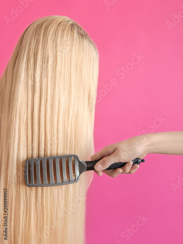 The hairstyling Concept photo for hairdresser's shop A girl is combing long blonde hair with hairbrush on a pink background