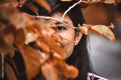 Portrait of Indian girl hiding face behind Orange leaves Wallpaper Mural