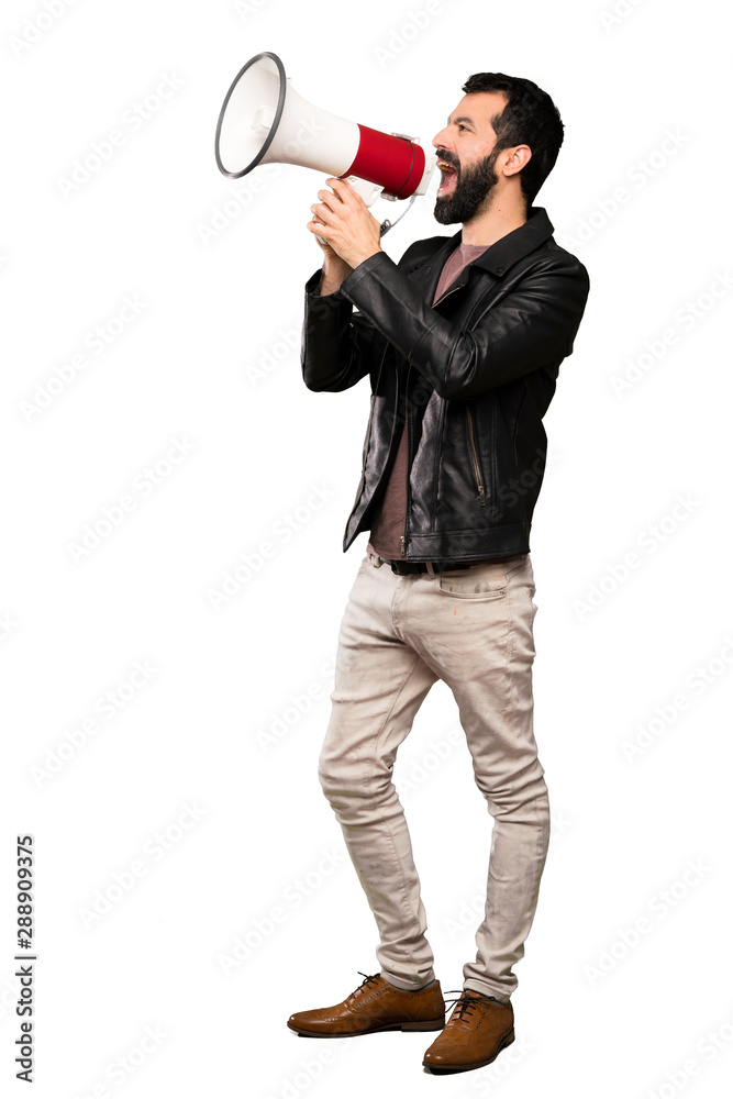 Fototapeta Handsome man with beard shouting through a megaphone over isolated white background