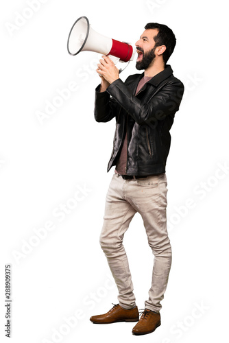 Handsome man with beard shouting through a megaphone over isolated white background - 288909375