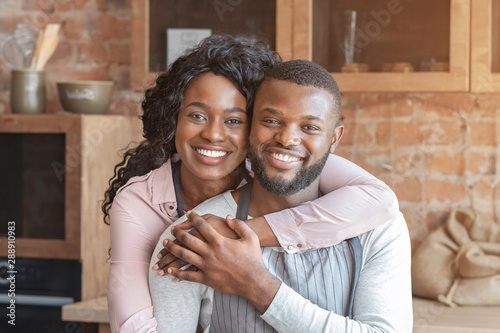 Photographie  Beautiful african woman hugging her husband at kitchen