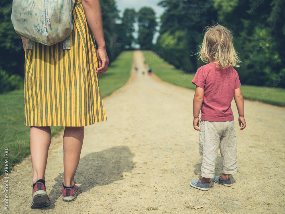 Fototapeta Mother and toddler standing on path in a park