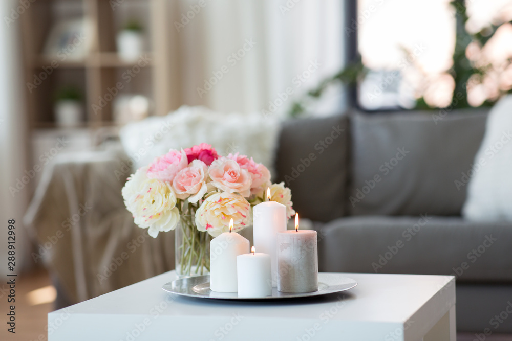 Fototapeta decoration, hygge and cosiness concept - candles burning on table and flowers at cozy home