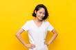 Asian young woman over isolated yellow wall posing with arms at hip and smiling