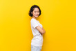 Asian young woman over isolated yellow wall with arms crossed and looking forward
