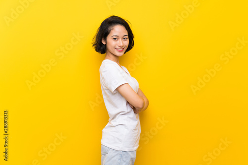 Carta da parati  Asian young woman over isolated yellow wall with arms crossed and looking forwar